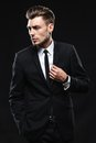Handsome young man in suit on dark background brunette a a Royalty Free Stock Photography
