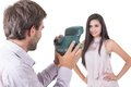 Handsome young man taking photos of beautiful girl men model with instant camera isolated on white Royalty Free Stock Image