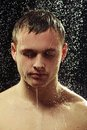 Handsome young man taking a shower after long day closeup portrait of standing under the running water and looking down Stock Images