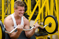 Handsome young man training biceps in gym lifting barbell on bench a Royalty Free Stock Photos