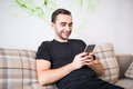 Handsome young man using his smartphone with smile while sitting on the couch at home Royalty Free Stock Photo