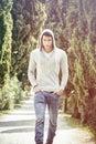 Handsome young man walking along rural road
