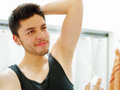 Handsome young man wearing black singlet top looking in mirror, applying deodorant during morning routine concept Royalty Free Stock Photo