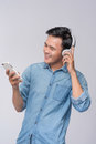 Handsome young man wearing headphones and holding mobile phone w Royalty Free Stock Photo
