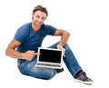 A handsome young man working on his laptop against while background Stock Images