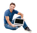 A handsome young man working on his laptop against while background Royalty Free Stock Image