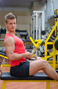 Handsome young man working out on gym equipment attractive and fit in doing pulley and exercising Stock Image