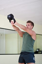 Handsome young man working out in gym with kettlebell attractive athletic exercising using Royalty Free Stock Photos