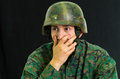 Handsome young soldier wearing uniform suffering from stress with his hand covering his mouth, in a black background Royalty Free Stock Photo