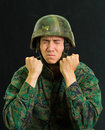 Handsome young soldier wearing uniform suffering from stress, pucker his face with both hands doing fist, in a black Royalty Free Stock Photo