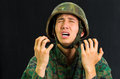 Handsome young soldier wearing uniform suffering from stress, screaming with both hands open, in a black background Royalty Free Stock Photo