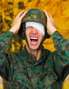 Handsome young soldier wearing uniform suffering from stress, with a white bandage around his head and covering his eye Royalty Free Stock Photo