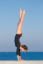 Handstand young gymnast on seashore Royalty Free Stock Photography