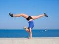 Handstand young gymnast on seashore Stock Photos