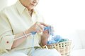 Handwork hands of elderly woman knitting woolen clothes Stock Photography