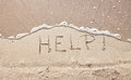 Handwriting message word help at sea beach sand Royalty Free Stock Photo