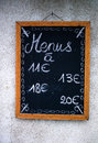 Handwritten french menu board hanging on a exterior wall showing different prices without specification of dishes Royalty Free Stock Photos