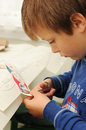 Handy child young cutting a transfer picture for wooden toy plain Stock Photo