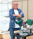 Handy man standing beside electric saw Stock Images