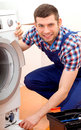 Handyman in blue uniform fixing a washing machine professional repairing bathroom Stock Image
