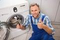 Handyman fixing a washing machine Royalty Free Stock Photo