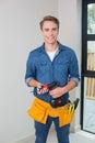 Handyman holding a drill with toolbelt around waist Royalty Free Stock Photo