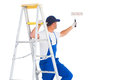 Handyman on ladder while using paint roller white background Stock Images