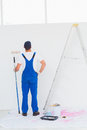 Handyman with paint roller examining wall at home Royalty Free Stock Photo