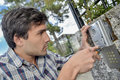 Handyman repairing intercom system Royalty Free Stock Photo