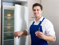 Handyman repairing refrigerator in kitchen Royalty Free Stock Photo