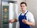 Handyman repairing refrigerator in kitchen Royalty Free Stock Photo