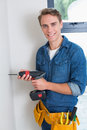 Handyman using a drill with toolbelt around waist Royalty Free Stock Photo