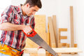 Handyman using saw confident young in workshop Stock Image
