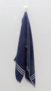 Hanging blue towel at suction cup hook on white tile wall in the bathroom Stock Photography