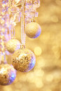 Hanging christmas ornaments over golden lights Royalty Free Stock Photography