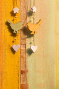 Hanging decor wood on string bird butterfly wooden birds hearts and strong over painted background Stock Photography