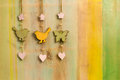 Hanging decor wood on string bird butterfly wooden birds hearts and strong over painted background Royalty Free Stock Image