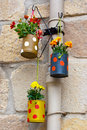 Hanging flowerpots made with cans in the street Royalty Free Stock Photo