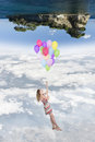 Hanging girl to a group of balloons flying toward a world upside Royalty Free Stock Photo