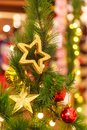 Hanging Gold Glittering stars and gift box baubles background with decorated green Christmas Tree in shopping mall. Special Royalty Free Stock Photo