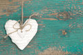 Hanging heart and turquoise wooden background in country style. Royalty Free Stock Photo