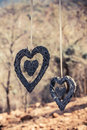Hanging hearts image of two woven wood in the outdoors on ribbon Royalty Free Stock Images