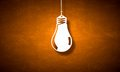 Hanging light bulb illuminating on dark background Royalty Free Stock Image