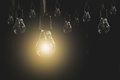 Hanging light bulbs with glowing one on dark background. Idea and creativity concept Royalty Free Stock Photo