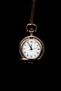 Hanging a minute vintage watch showing five to twelve over black background concept of Royalty Free Stock Images
