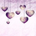 Hanging small violet hearts with triangle pattern and lace like outline on graphic background Stock Photos