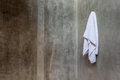 Hanging white towel draped on exposed concrete wall in the bathr Royalty Free Stock Photo