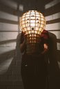 Hanging wooden light shade lamp with bulb in hands Stock Photo