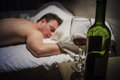 Hangover man in a bed at night with wine bottle foreground Stock Photography