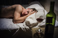 Hangover man with headaches in a bed at night and wine bottle Royalty Free Stock Images